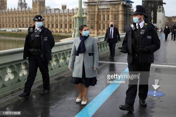 British Home Secretary Priti Patel walks across Westminster Bridge toward St Thomas' Hospital with two police officers on January 18, 2021 in London,...