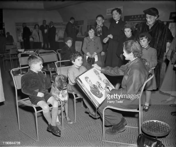 British illustrator Elva Blacker painting sketched portraits of 6yearold Sally Johns of Palmers Green and Michael Clementson of New Southgate with...
