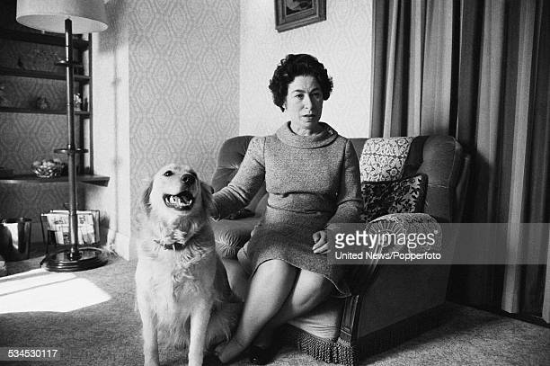British impersonator and lookalike actress of Queen Elizabeth II Jeannette Charles pictured with a dog in a domestic living room on 5th March 1976