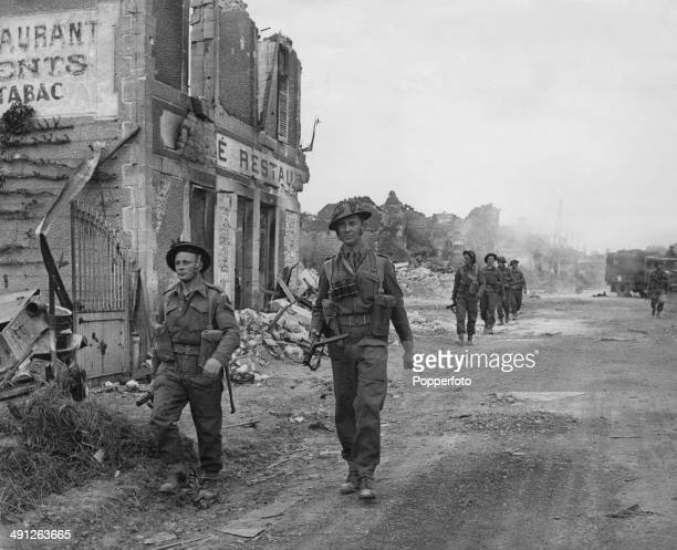 British infantry of 'A' Company 6th Durham Light Infantry 50th Division march through the village of Douet following the capture of Bayeux during the...