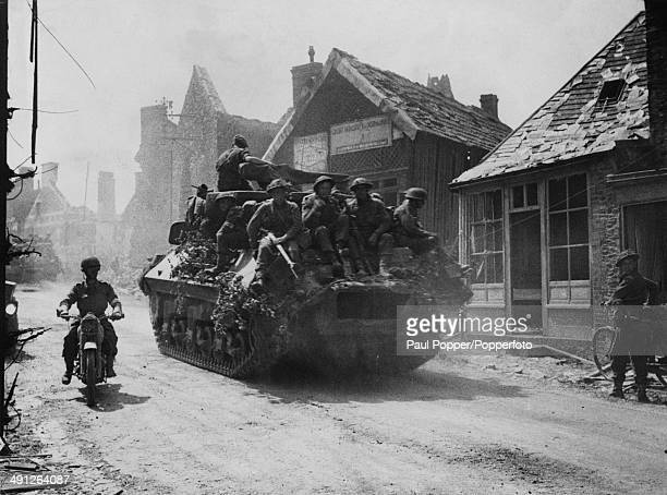 British infantry riding on a Sherman tank through the village of Caumontl'Evente south of Caen during the Allied invasion of Normandy August 1944