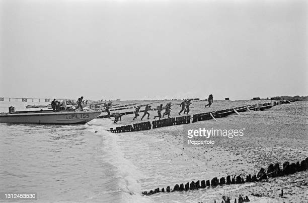 British infantry troops exit an armoured Royal Navy Landing Craft Personnel as part of a large scale amphibious landing invasion exercise on a beach...