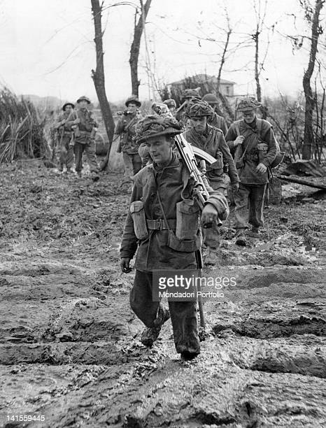 A British infantry unit advancing over muddy terrain near the River Rubicon Emilia Romagna October 1944