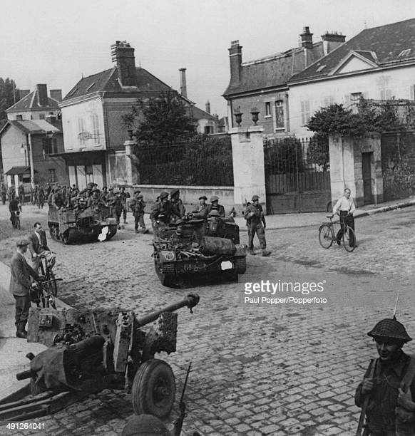 British infantry with antitank guns and bren gun carriers enter a village after crossing pontoon and Bailey bridges over the River Seine at Vernon...