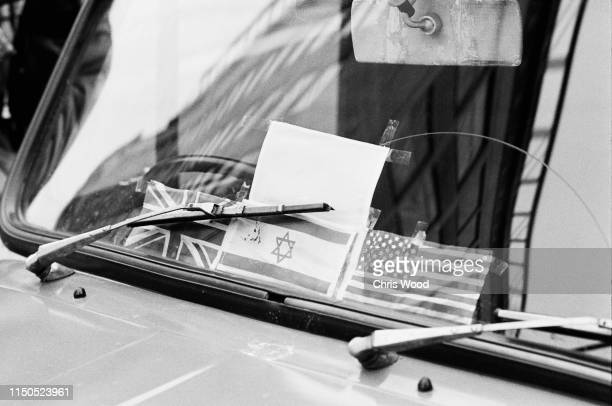 British Israeli and US flags on the dashboard of a Morris Minor van parked on Waterloo Place near the cordonedoff Charles II Street entrance to St...