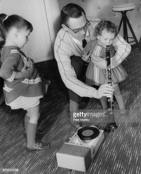 British jazz clarinettist and bandleader Terry Lightfoot plays with his daughters Sharon Theresa and Michele Bernadette at their home in Potter's Bar...