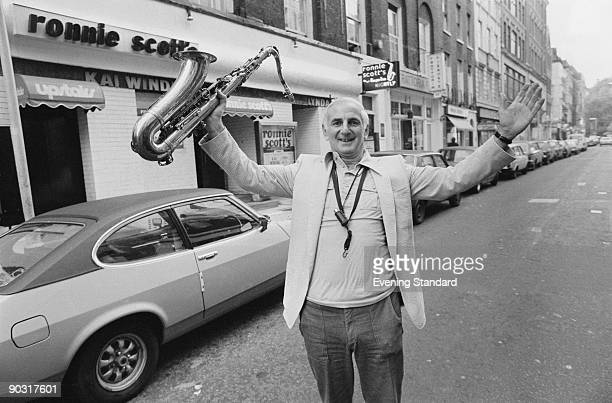 British jazz musician Ronnie Scott poses with a saxophone outside his jazz club in Soho London October 1979