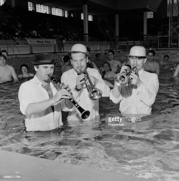 British jazz musicians from left Acker Bilk Ken Colyer and Kenny Ball pictured together playing their instruments in the water at the Derby Baths...