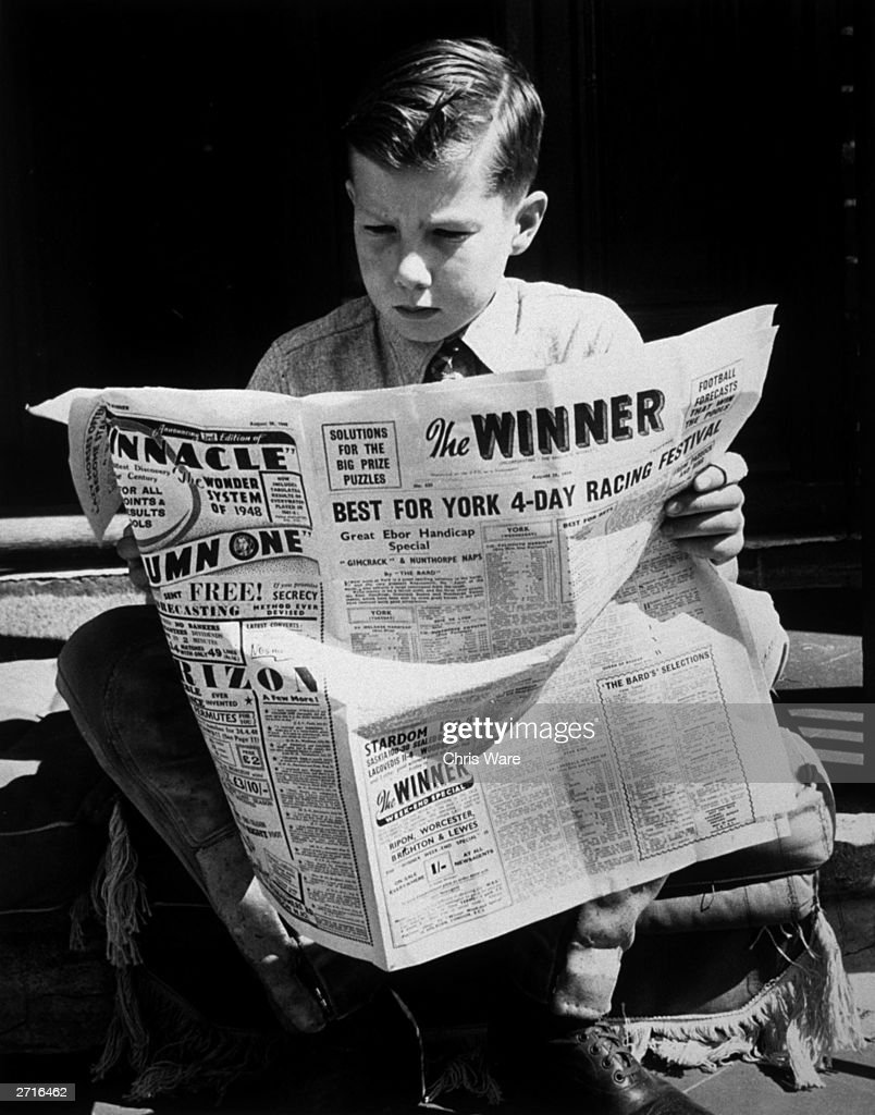 British jockey Lester Piggott, aged 12, reading his favourite newspaper 'The Winner' which gives him all the racing news. He is at his father's stables in Lambourn, Berkshire.