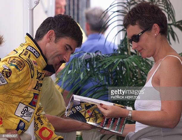 British Jordan-Mugen-Honda driver Damon Hill reads a magazine with his wife Georgie in the paddocks of the Silverstone racetrack, 08 July 1999, three...