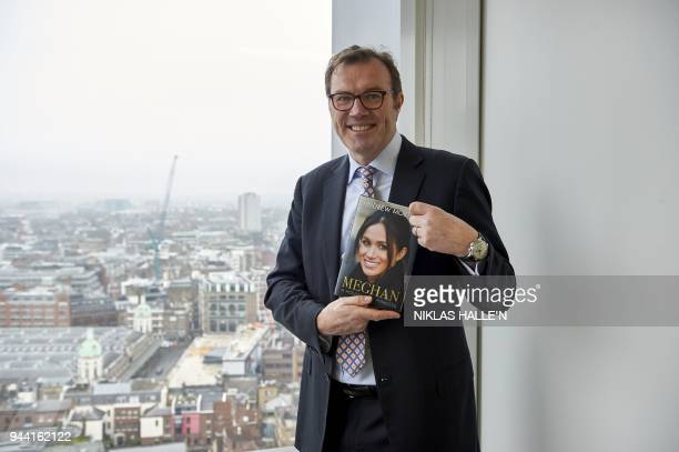 British journalist and writer Andrew Morton holds a copy of his biography of US actress and fiancee of Britain's Prince Harry Meghan Markle as he...