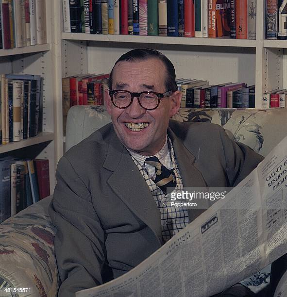 1968 British journalist and writer MacDonald Hastings posed at home reading a newspaper in his library in 1968