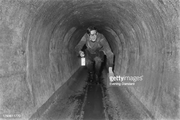 British journalist Max Hastings crawls through a pipe, UK, 27th January 1967.