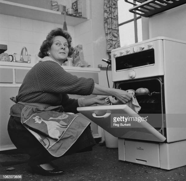 British Labour councilor and campaigner Audrey Callaghan wife of James Callaghan pushing a tray of baked potatoes in an oven UK 26th January 1963