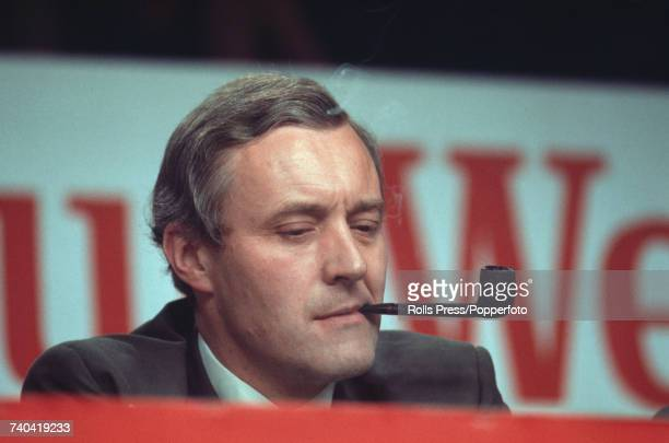 British Labour Party politician and Chairman of the Labour Party Tony Benn pictured smoking a pipe on the platform at the Labour Party annual...