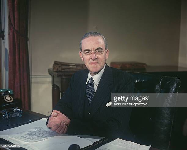 British Labour Party politician and Chancellor of the Exchequer Sir Stafford Cripps pictured sitting at his desk in the Treasury in London in...