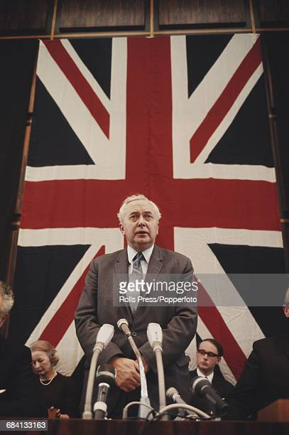 British Labour Party politician and Prime Minister of the United Kingdom Harold Wilson speaks in front of a union flag at a press conference during a...