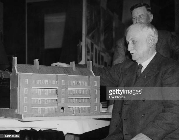 British Labour politician and social reformer George Lansbury the MP for Bow and Bromley examines a model of a block of flats built by the Stepney...