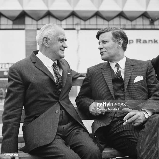 British Labour politician Michael Stewart, Baron Stewart of Fulham and Helmut Schmidt sitting outdoors on seafront in Brighton for the Labour Party...