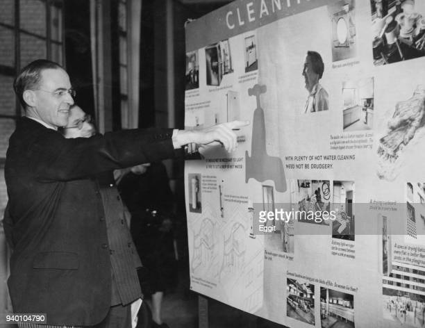 British Labour politician Sir Stafford Cripps views a display on effective cleaning after opening an exhibition on domestic planning and design at St...