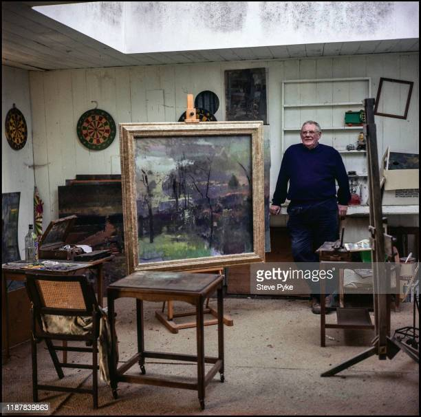 British landscape painter, Fred Cuming, with some of his work in his studio, Rye, East Sussex, 7th March 2000.