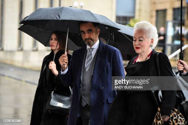 British lawyer Aamer Anwar arrives with members of his team at a venue in Glasgow on November 24, 2020 to take part on the opening day of a...
