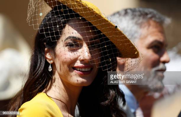 TOPSHOT British lawyer Amal Clooney arrives with her husband US actor George Clooney for the wedding ceremony of Britain's Prince Harry Duke of...