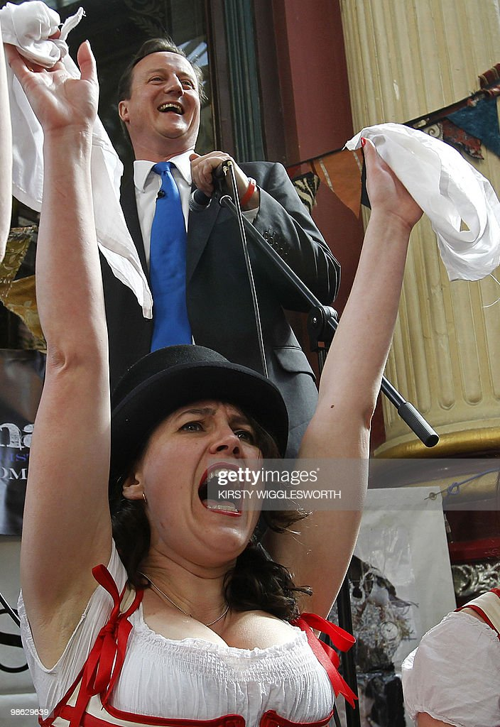 British leader of the oppostion Conservative party, David Cameron (top) speaks from behind a line of folk dancers, to members of the public celebrating St George's Day, during an election campaign visit to Leadenhall Market in central London on April 23, 2010. AFP PHOTO/Kirsty Wigglesworth/Pool