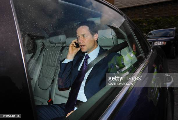 British Liberal Democrat Leader Nick Clegg speaks on his mobile phone as he is driven from the Houses of Parliament in central London on May 10,...