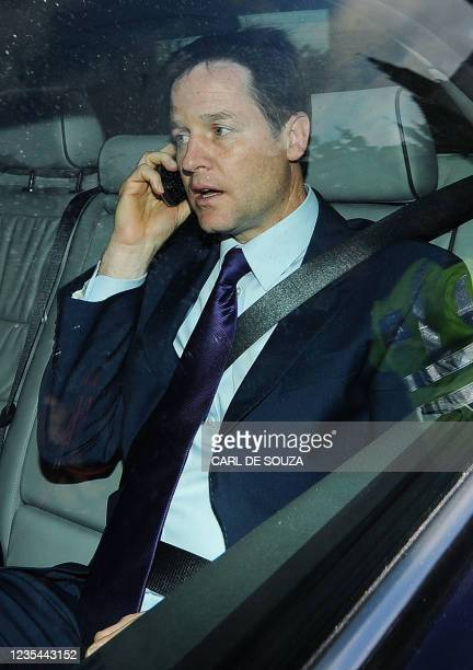 British Liberal Democrat Leader Nick Clegg uses his mobile phone as he is driven from the Houses of Parliament in central London on May 10, 2010....