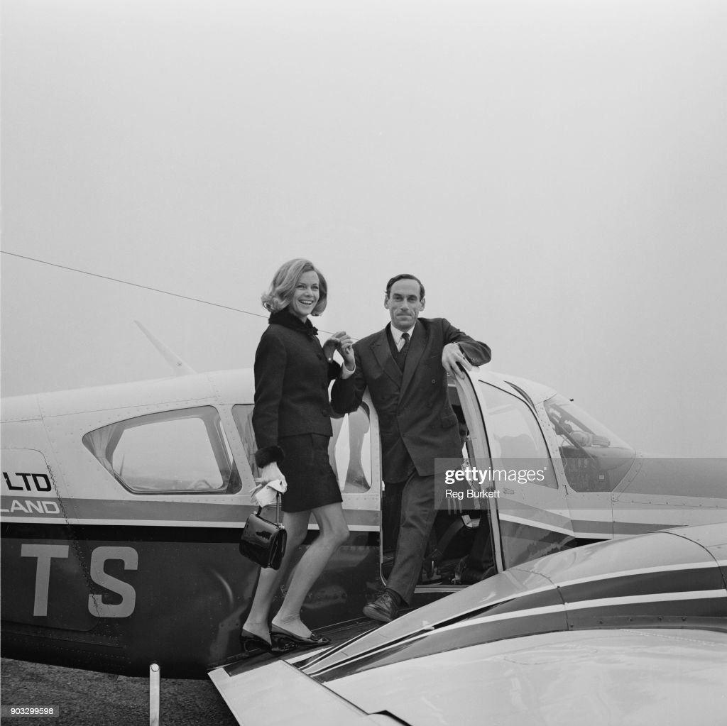 British Liberal Party politician Jeremy Thorpe helps British actress Honor Blackman aboard flight aircraft, UK, 21st October 1968.