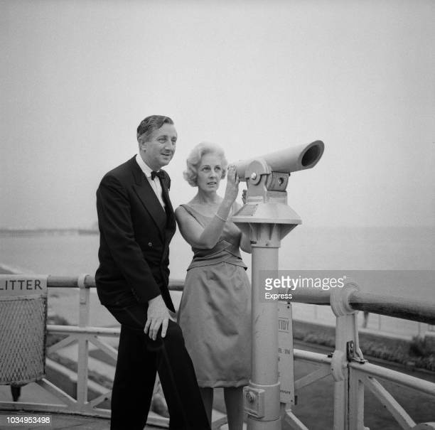 British Liberal Party politician Ronald GardnerThorpe pictured with his wife Hazel as they look through a viewing telescope on the seafront during...