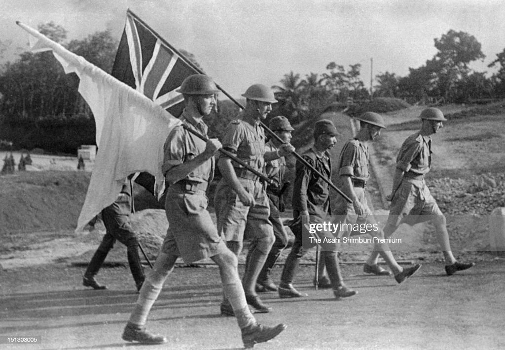 British Lieutenant General Arthur Ernest Percival (right end), General Officer Commanding Malaya in World War Two, on march towards the Japanese camp to surrender Singapore, bearing the Union Jack and the white flag, on February 15 1942.