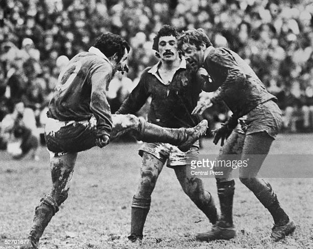 British Lions captain Phil Bennett kicks for touch before being tackled by Paul Quinn and Mark Stevens of Wellington during a match in New Zealand...