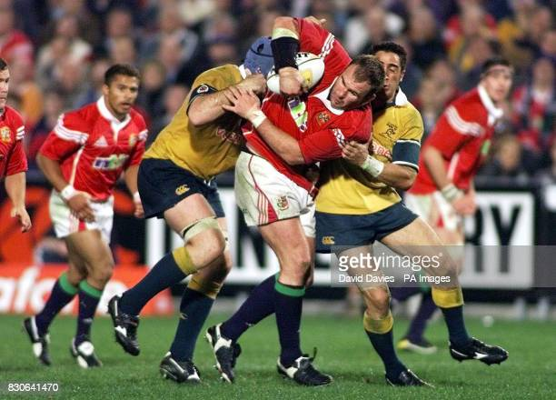 British Lions' Scott Quinell surges through the challenge of Australia A's captain David Lyons and Manuel Edmonds during their international tour...