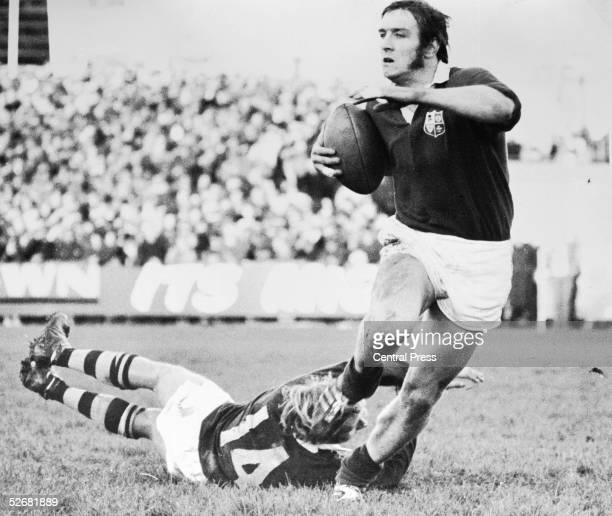 British Lions winger John Bevan avoids a desperate tackle by his Otago opposite number Bruce Anthony Hunter during a match against Otago which the...