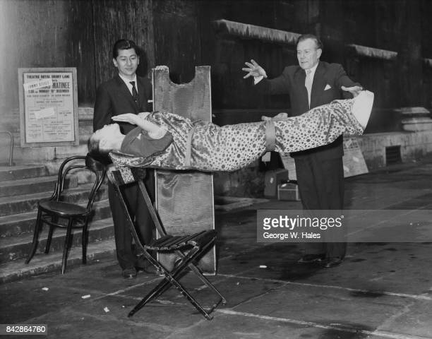 British magician Robert Harbin performs a feat of levitation on Japanese dancer Miss Nippon outside St MartinintheFields London 15th December 1960