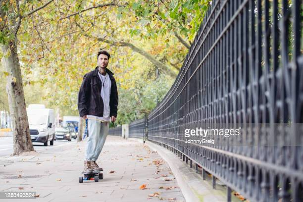 british male skateboarder riding along thames embankment - real people stock pictures, royalty-free photos & images