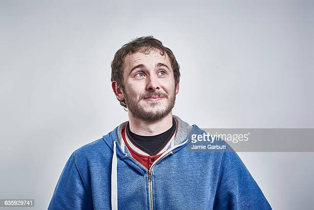 british male with a slight smile looking up - hooded shirt stock pictures, royalty-free photos & images