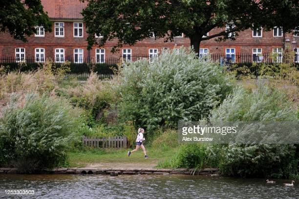 British marathon runner Charlotte Purdue runs next to the River Thames as Hampton Court Palace is seen in the background during a training session on...
