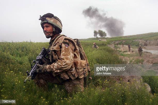 British Marine Justin Montague from Swindon England watches for Taliban movements after an airstrike was called in on a Taliban position on March 18...