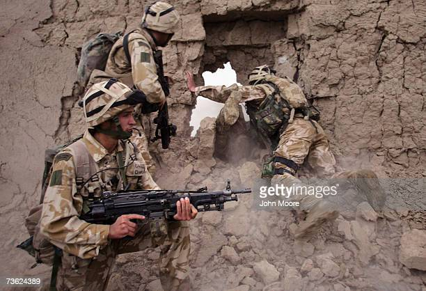 British Marines crawl through a hole after blasting through a wall during a morning anti-Taliban operation on March 18, 2007 near Kajaki in the...