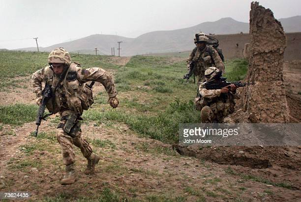 British Marines run under fire from Taliban during a morning operation on March 18 2007 near Kajaki in the Afghan province of Helmand Members of the...