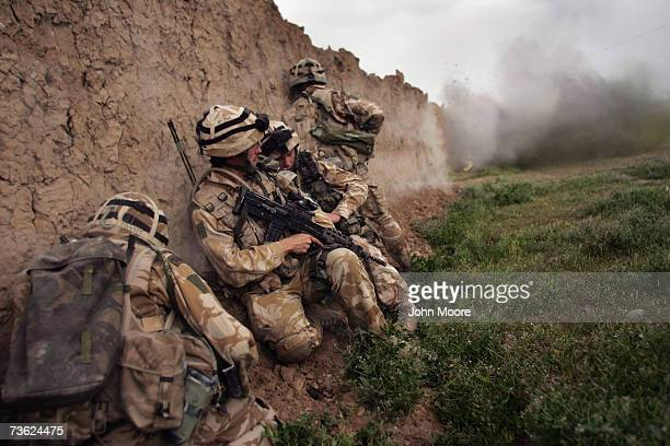 British Marines take cover while blasting a whole in a wall during an antiTaliban operation near Kajaki in the Afghan province of Helmand March 18...