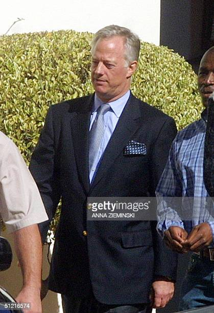 British Mark Thatcher is escorted by members of the Scorpions unit to an awaiting car at his home in constantia Cape Town 25 August 2004 The son of...
