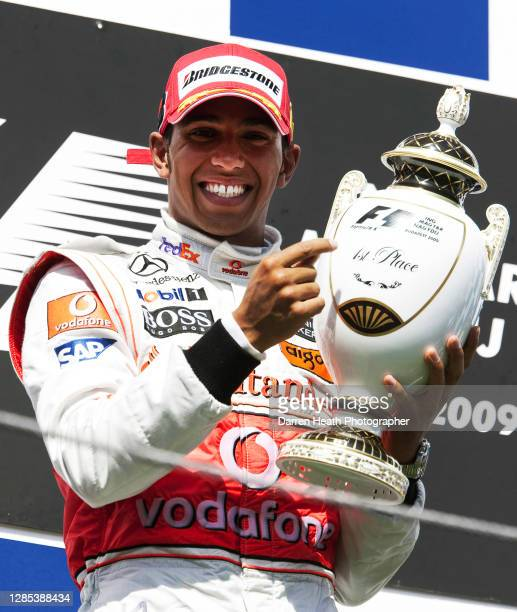 British McLaren Formula One driver Lewis Hamilton celebrates on the winners podium by raising the race winners trophy after winning the 2009...