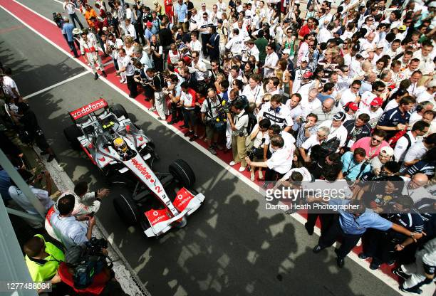 British McLaren Formula One driver Lewis Hamilton drives his MP4-22 car along the pit lane past his celebrating team after claiming his first Grand...