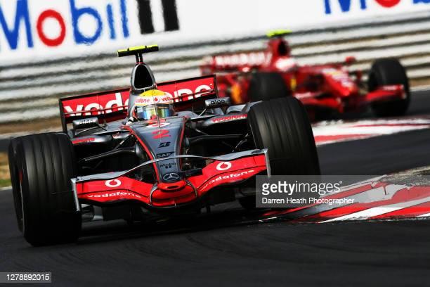 British McLaren Formula One driver Lewis Hamilton drives his MP4-22 car ahead of Kimi Raikkonen in his Ferrari F2007 car during 2007 Hungarian Grand...