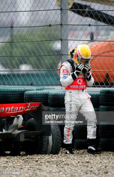 British McLaren Formula One driver Lewis Hamilton walks away from his beached McLaren MP4-22 car as he retires from the 2007 Chinese Grand Prix held...
