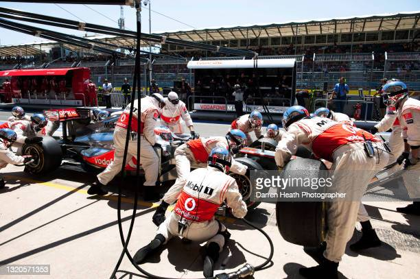 British McLaren Formula One racing driver Jenson Button sitting in his MP4-26 racing car in the McLaren team's pit lane, pit stop box as the crew of...